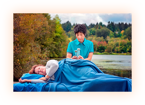 Sandra Lee working on massage client, tuning forks, water and trees background, blue shirt, blue blanket