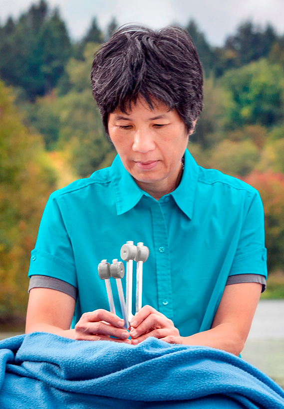 Sandra Lee working on massage client, tuning forks, trees background, blue shirt, blue blanket