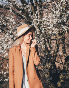 smiling woman in a coat and hat, smelling flowers, tree with white flowers