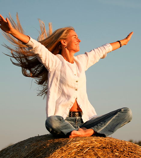 woman smiling arms raised, sunrise, sunlight, hair flying, sitting cross legged on hay bale