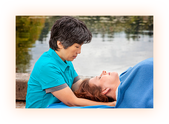 Sandra Lee working on massage client, water background, blue shirt, blue blanket