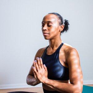 black woman meditating, prayer pose
